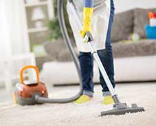 Putzfrau saugt mit dem Staubsauger einen Teppich